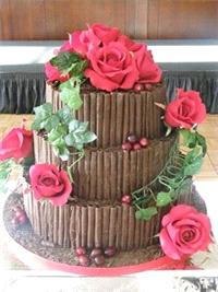Cakes. 3 tier cake covered in Dark Chocolate Curls and decorated with Red roses and Ivy