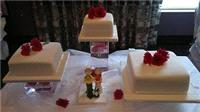 Cakes. 3 tiers displayed on clear vases filled with water with  fresh Gerbera flowers floating  insi