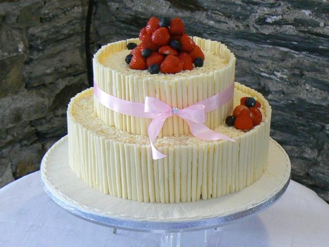 Wedding cakes, The sides of this wedding cake are decorated with white chocolate curls. The top is f