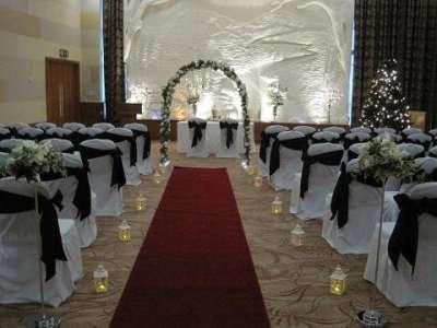 Civil Ceremonies, Covered chairs wrapped in black ribbon and candle lit.