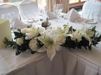 Center pieces, A white silk flower in an arrangement suitable for the top table at a wedding.