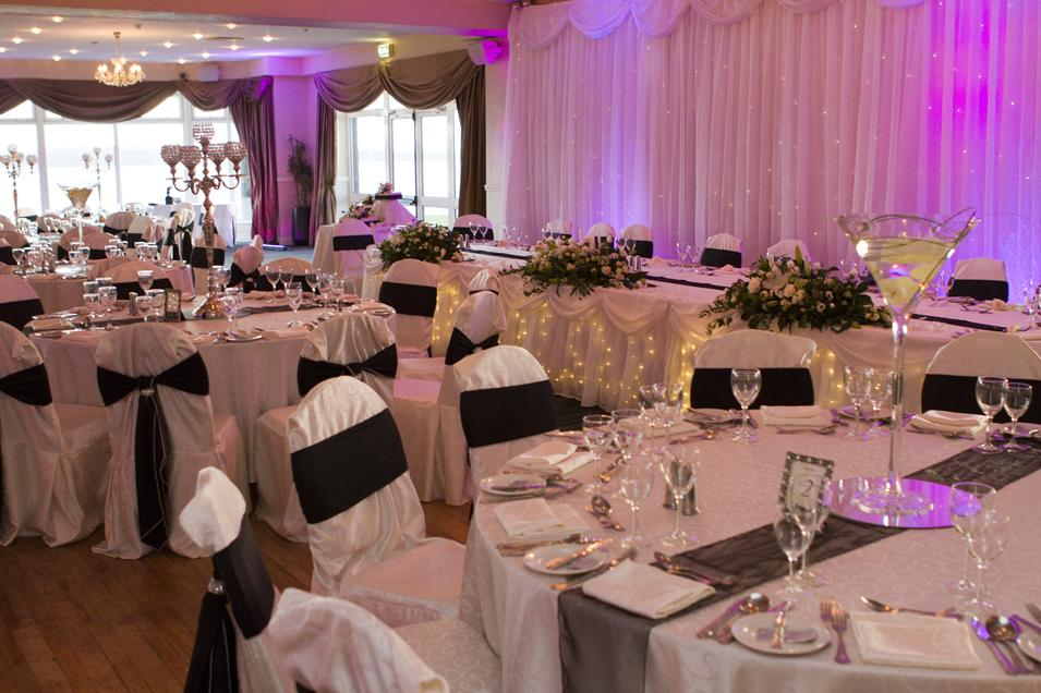Reception Decor, White chair covers with a black sash. Affect lighting.