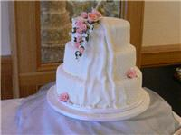 Cakes. Filigree Cascade Wedding Cake with Cloth & Flowers (eight different cake flavours available).