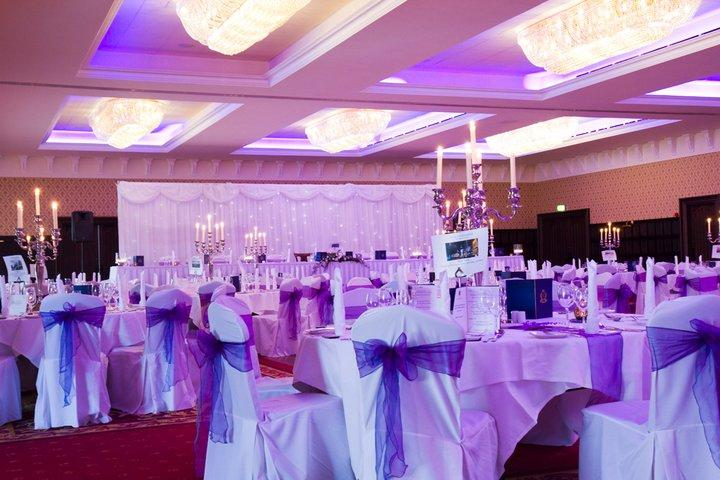 Chair Covers, White chair covers tied with a purple sash.