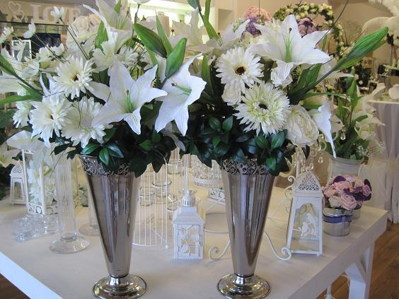 Flowers, Pair of silver urns with an ivory and white silk floral.