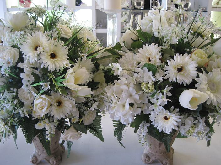 Flowers, Pair of stone urns filled with an ivory and white silk floral arrangment.