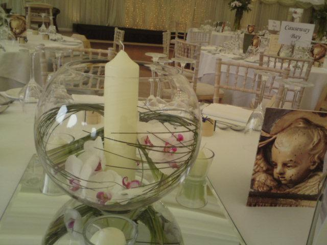 Center Pieces, A round vase containing a candle and orchids.
