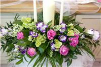 Flowers. Flower arrangement around candle holder. Large range of fresh cut flowers and plants availa
