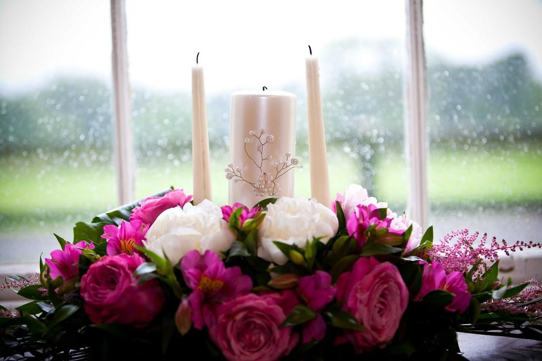 Flowers, Flower arrangement around candle holder. Large range of fresh cut flowers and plants availa