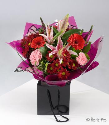 Flowers, Scarlet. Hand-tied bouquet of mixed red and pink flowers. Only available in our local deliv