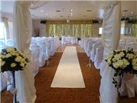 Decor & Event Styling. White fabric arch with white rose floral arrangements.