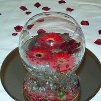 Centerpieces, Flowers floating in water in a round glass vase.