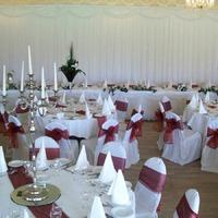 Decor & Event Styling. White table linen with red table runners and red satin sash ties.