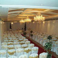 Ceremony Decor, White chair covers with satin ties floral pew ends and mood lighting.