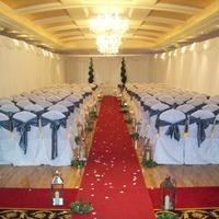 Ceremony Decor, White chair covers with dark grey ties red carpet and candles.