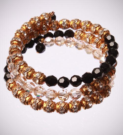 Jewellery, Black and Gold Bracelet. This bracelet is designed on a spring wire that wraps around the
